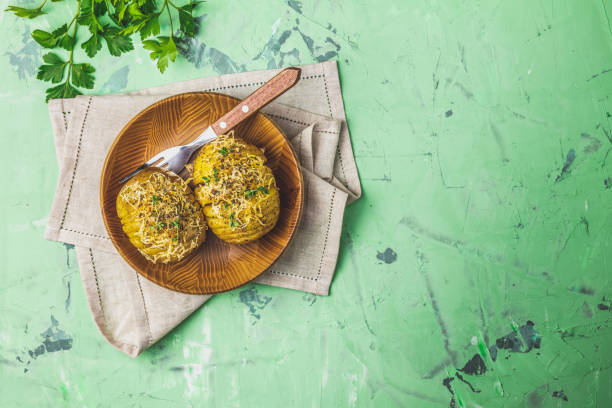 Baked potatoes in wooden plate with green onion and cheese stock photo