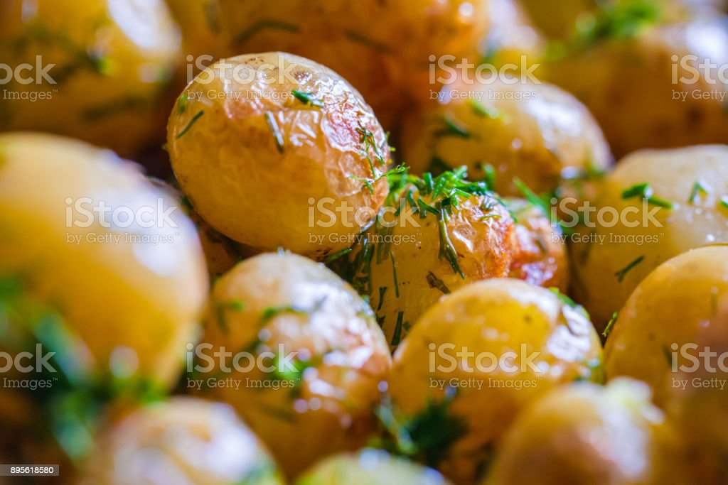 Baked potatoes (jacket potatoes) whole in their skins with sunflower oil and dill until  golden brown . Close up. stock photo