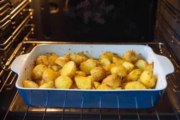 Gebackene Kartoffeln mit Kurkuma und anderen Gewürzen in Bräter – Foto