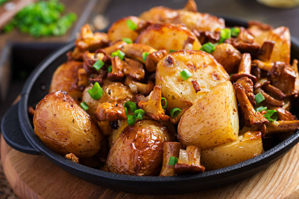 Baked potatoes with garlic, herbs and fried chanterelles in a cast iron skillet. stock photo