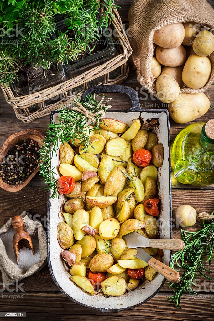 Baked potatoes with rosemary and garlic stock photo