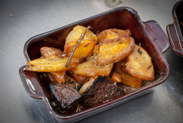 Baked potatoes with rosemary in a brown bowl - foto stock