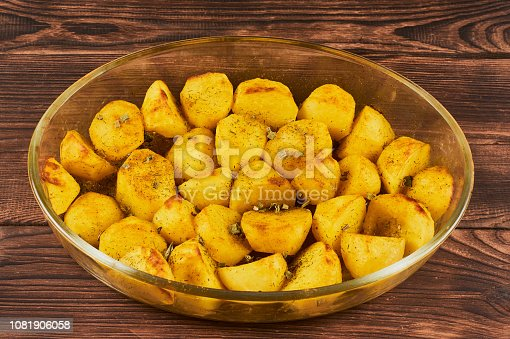 Baked Spiced Potatoes in cookware on a brown wooden bakground, close-up