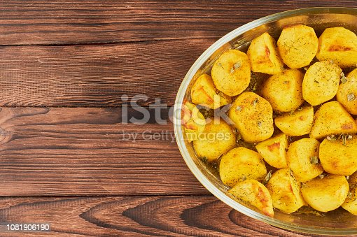 Baked Spiced Potatoes in cookware on a brown wooden bakground, falt lay