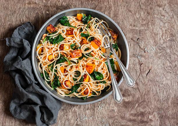baked pumpkin and spinach spaghetti in a frying pan - spaghetti mit spinat stock-fotos und bilder