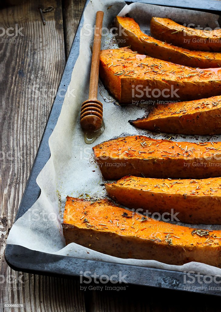 Baked pumpkin on a baking tray with dried rose foto royalty-free