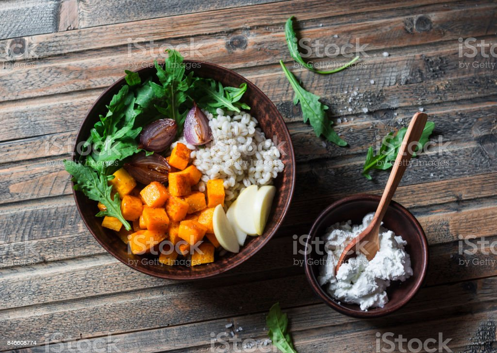 Baked pumpkin, red onions and barley vegetarian bowl on wooden table, top view. Vegetarian food concept stock photo