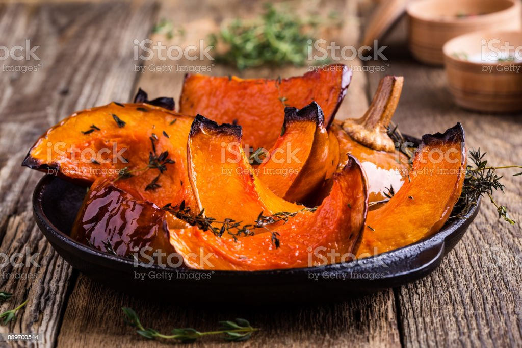 Baked pumpkin with thyme in cast iron skillet stock photo