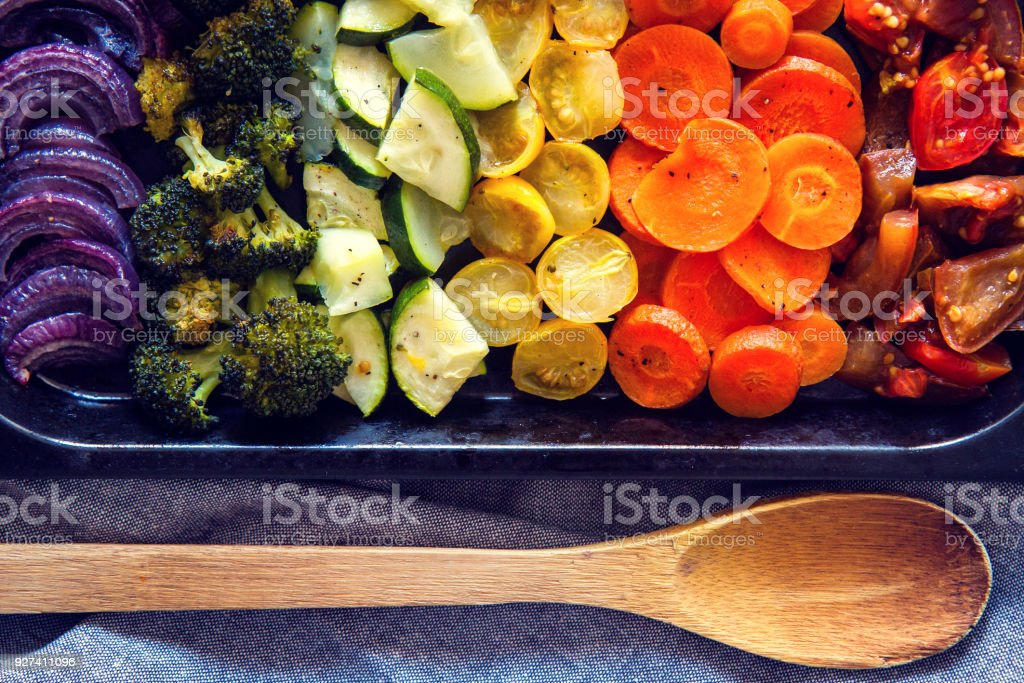 Baked rainbow vegetables composed of onion, broccoli, zucchini, tomatoes and carrot. stock photo
