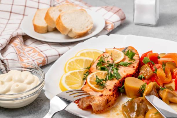 Gebackene Lachsfilet-Medaillon mit Salat aus eingelegtem Gemüse und Pilzen auf einem weißen Teller auf grauem Hintergrund – Foto