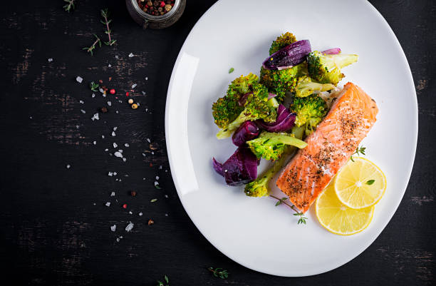 Baked salmon fillet with broccoli, red onion and lemon. Top view, overhead stock photo