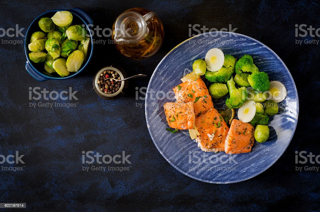 Baked salmon fish garnished with broccoli and Brussels sprouts stock photo
