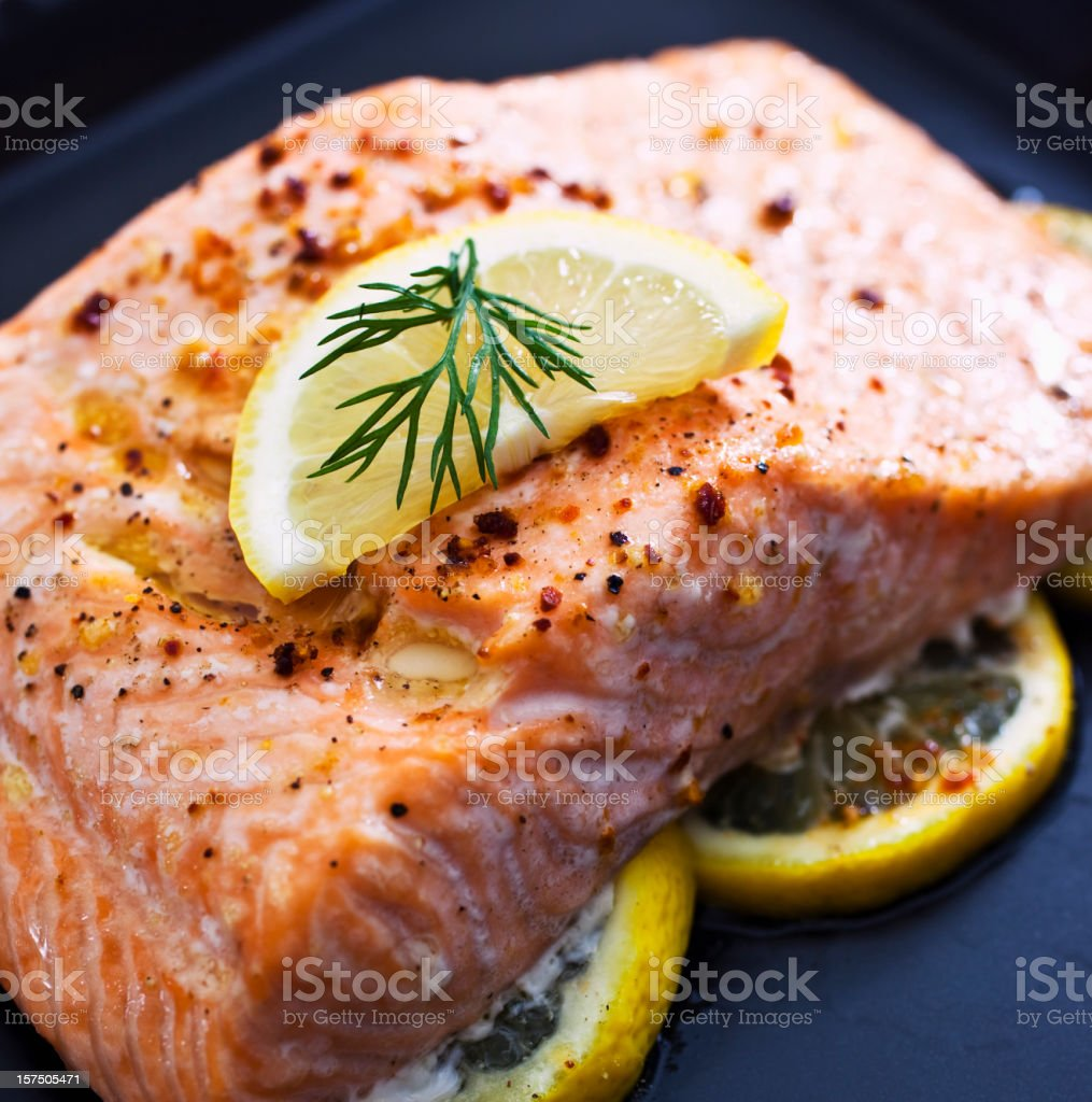 Baked salmon garnished with a slice of lemon royalty-free stock photo