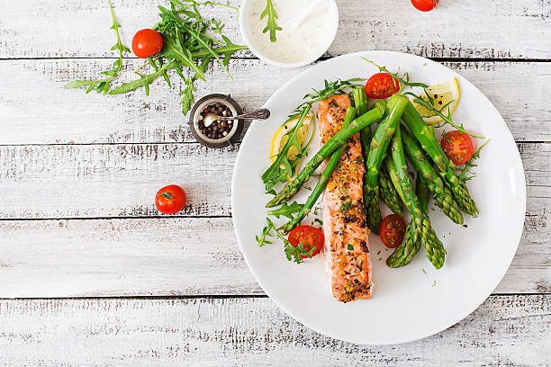 baked salmon garnished with asparagus and tomatoes with herbs - crockery stock photos and pictures
