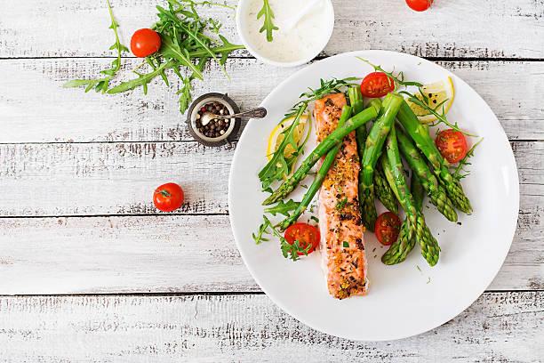 salmão assado no forno guarnecido com espargos e tomates com plantas aromáticas - meat plate imagens e fotografias de stock