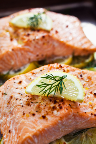 Baked Salmon on a bed of lemon slices. Shot on a baking sheet. Selective focus.