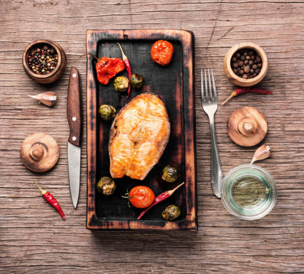 Baked salmon steak Grilled salmon with tomato, pepper and cabbage.Fish steak with vegetable garnish.Grilled fresh fish.Beautiful festive dish atlantic salmon stock pictures, royalty-free photos & images