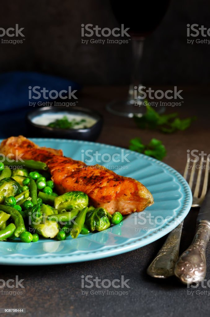 Baked salmon steak with asparagus, Brussels sprouts and green peas on a concrete background with a glass of wine. stock photo