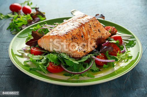 Baked salmon steak with tomato, onion, mix of green leaves salad in a plate. healthy food.