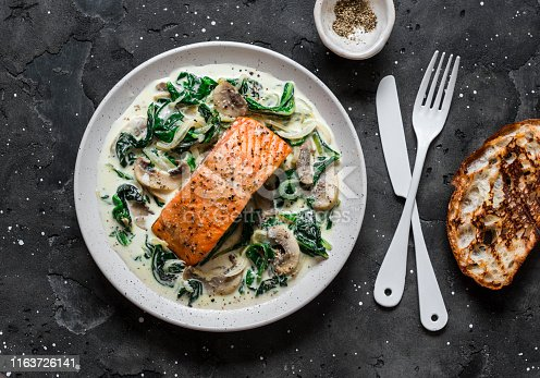 Baked salmon with creamy spinach mushrooms sauce on a dark background, top view. Salmon florentine