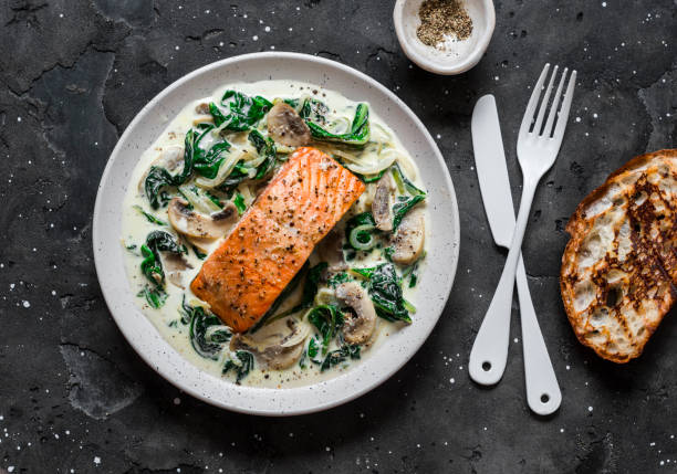 Baked salmon with creamy spinach mushrooms sauce on a dark background, top view. Salmon florentine Baked salmon with creamy spinach mushrooms sauce on a dark background, top view. Salmon florentine crockery stock pictures, royalty-free photos & images