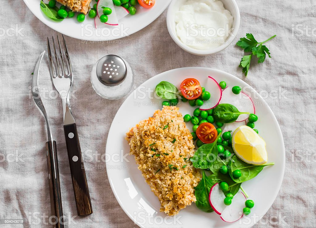 Baked salmon with lemon bread crust and fresh vegetable salad stock photo