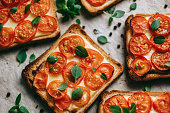 Baked sandwich with cheese and cherry tomatoes on dark bread decorated with fresh basil leaves. High quality photo