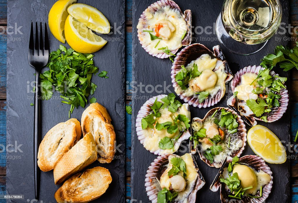 Baked scallops on slate with lemon, cilantro, bread white wine stock photo
