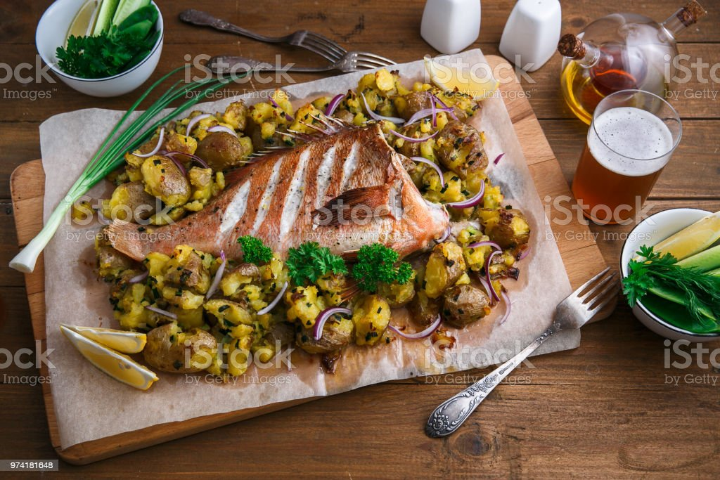 Baked sea perch or red grouper with potatoes, top view stock photo