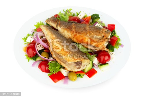 Baked seabass with greek salad mediterranean cuisine on white plate isolated on white background