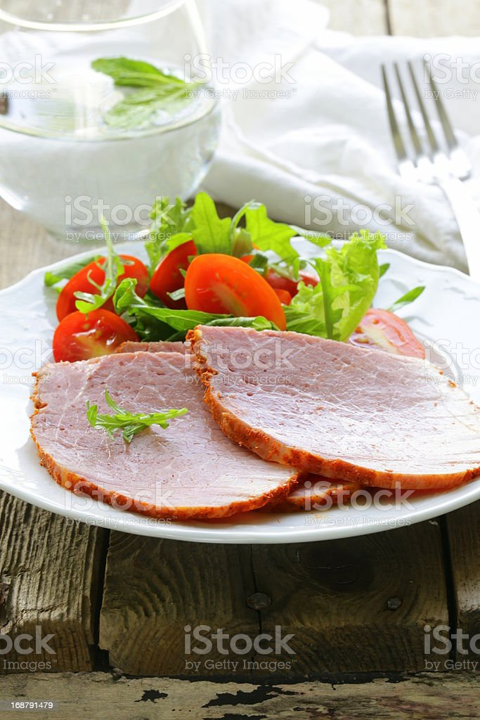 Baked sliced ham served with green salad royalty-free stock photo