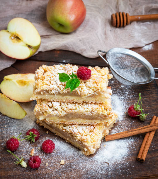 baked slices of pie with apples on a brown wooden board stock photo