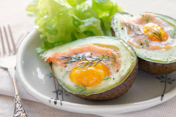 Baked smoked salmon, egg in avodaco, ketogenic keto low carb diet food stock photo