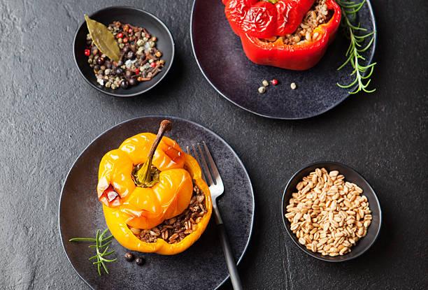 gebackene gefüllte paprika mit dinkel weizen, reis, gemüse - griechischer couscous salat stock-fotos und bilder