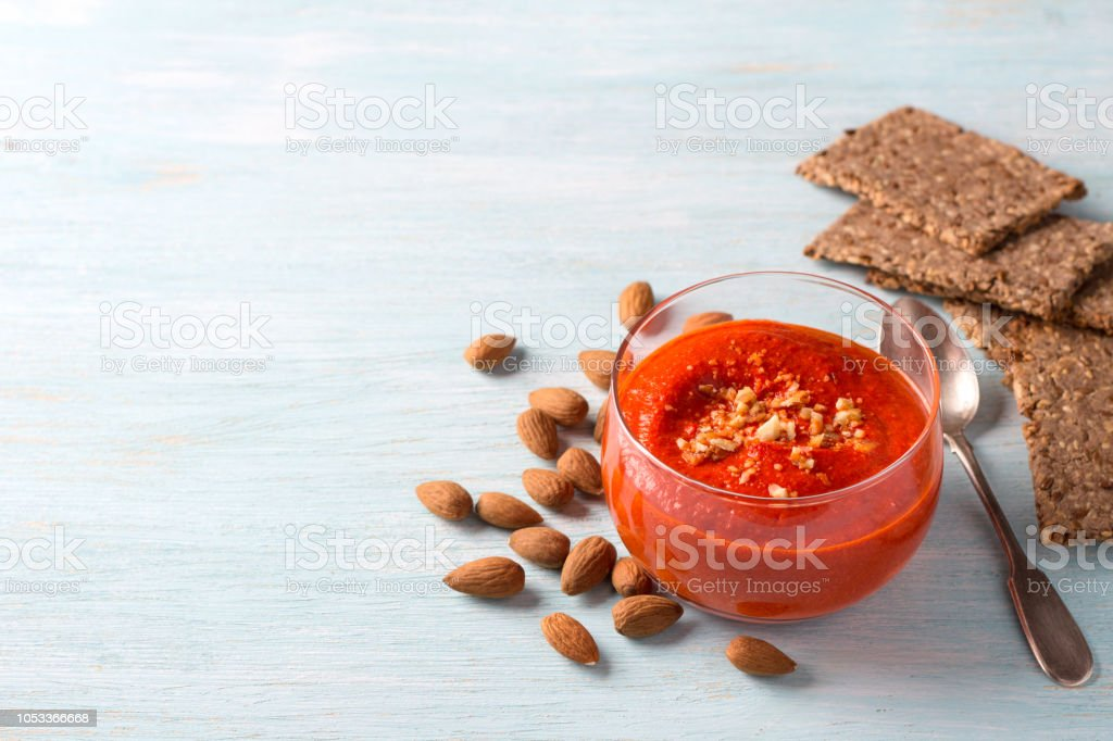 Baked sweet bell pepper dip with almonds with homemade flaxseed flat bread on a light blue background stock photo