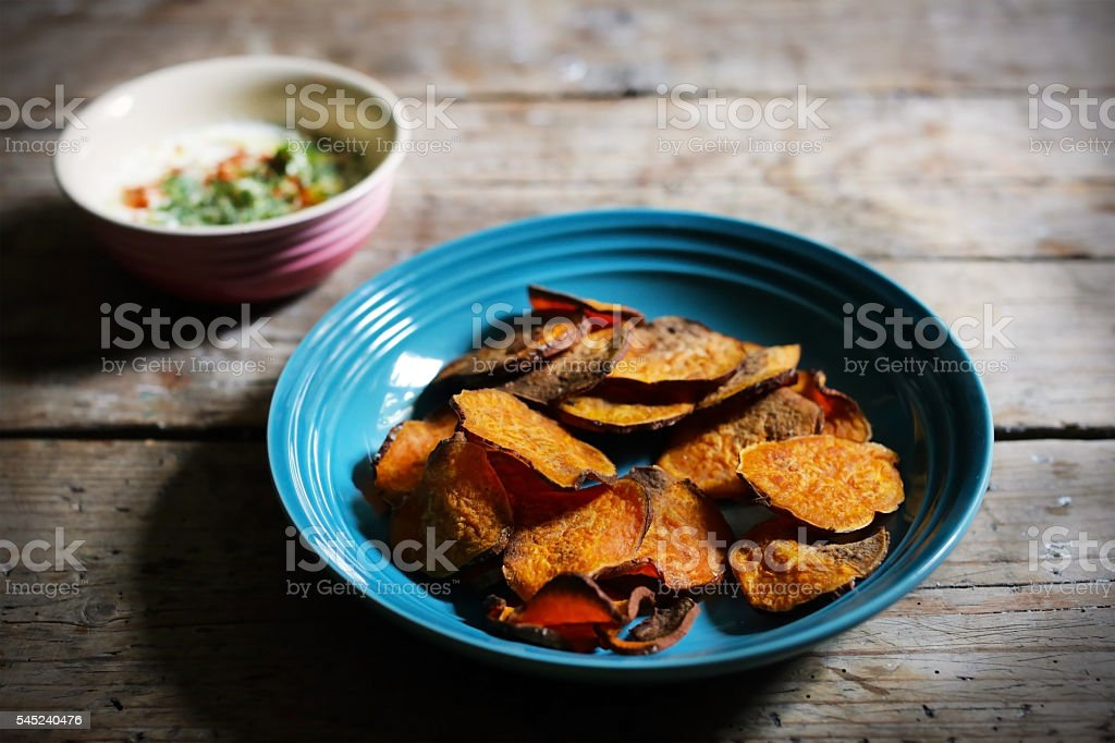 Baked sweet potato chips, homemade, with vegan dip stock photo