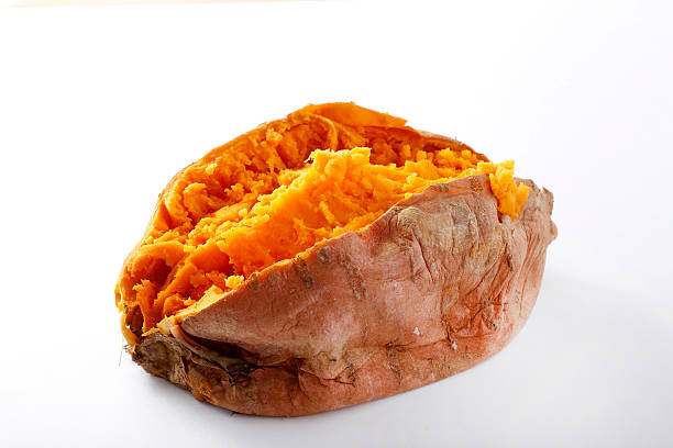 a baked sweet potato with a white background - gebakken in de oven stockfoto's en -beelden