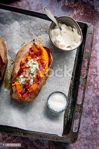 Baked sweet potato or yam split open after baking filled with sour cream, chives and bacon. Overhead view looking down, photographed on a baking tray with baking parchment on it, colour, vertical with some copy space. With a side bowl of soured cream or creme fraiche and salt.