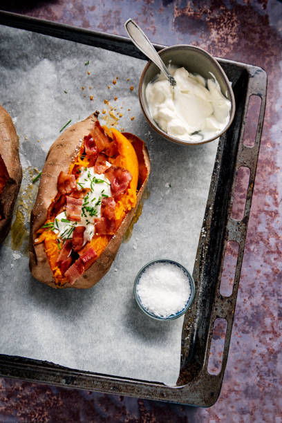 Baked sweet potato with sour cream, chives and bacon. Baked sweet potato or yam split open after baking filled with sour cream, chives and bacon. Overhead view looking down, photographed on a baking tray with baking parchment on it, colour, vertical with some copy space. With a side bowl of soured cream or creme fraiche and salt. sweet potato stock pictures, royalty-free photos & images
