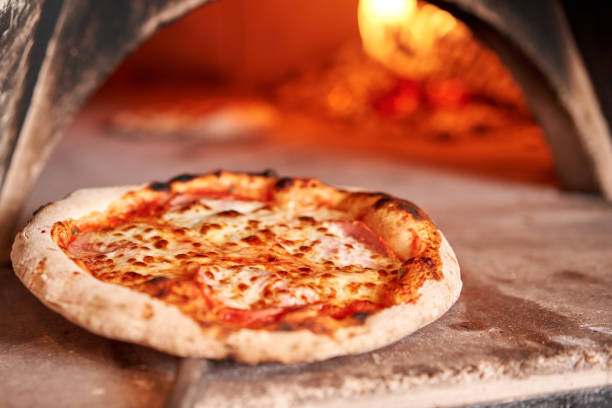 Baked tasty margherita pizza in Traditional wood oven in Naples restaurant, Italy. Original neapolitan pizza. Red hot coal. stock photo