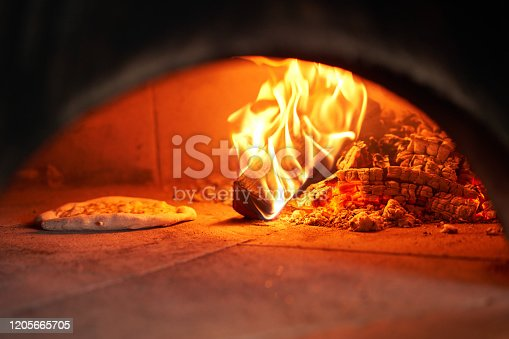 Baked tasty margherita pizza in Traditional wood oven in Naples restaurant, Italy. Original neapolitan pizza. Red hot coal