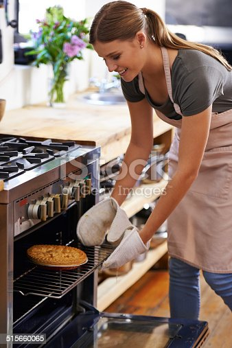 Shot of an attractive young woman taking out a baked pie from the oven