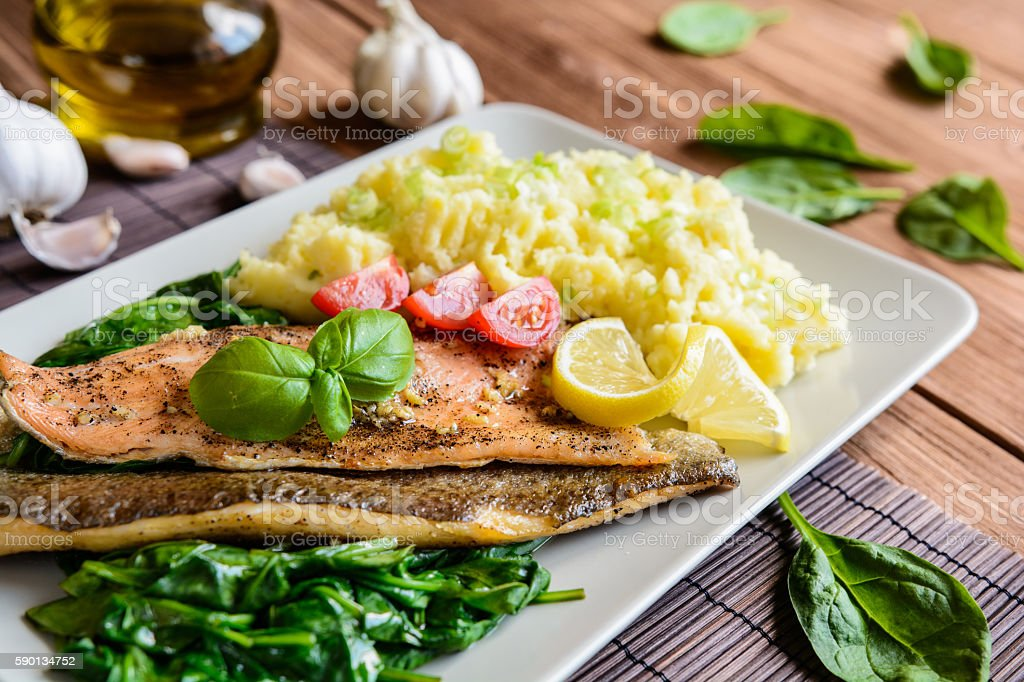 Baked trout fillet with mashed potatoes and steamed spinach stock photo
