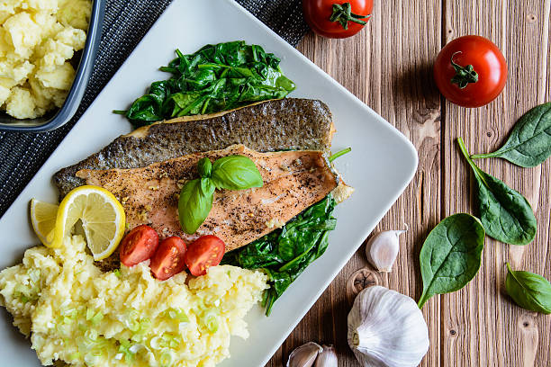 baked trout fillet with mashed potatoes and steamed spinach - trout foto e immagini stock