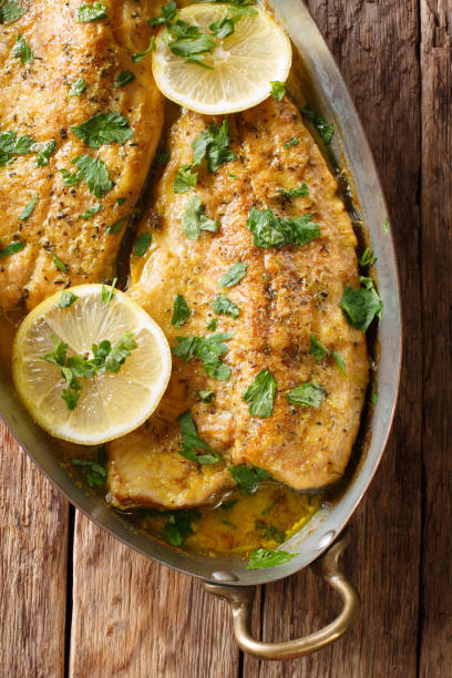 baked trout fish with garlic lemon butter sauce, parsley closeup in a copper pan on a table. vertical top view - trout foto e immagini stock