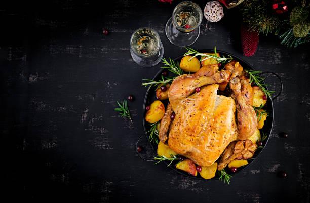 Gebackener Truthahn oder Huhn. Der Weihnachtstisch wird mit einem Truthahn serviert, der mit heller Insel geschmückt ist. Gebratenes Huhn. Tabelleneinstellung. Weihnachtsessen. Ansicht von oben – Foto