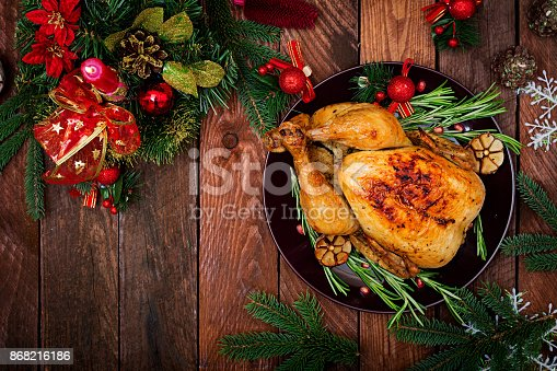 istock Baked turkey or chicken. The Christmas table is served with a turkey, decorated with bright tinsel and candles. Fried chicken, table. Christmas dinner. Flat lay. Top view 868216186