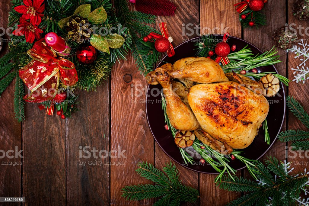 Gebackener Truthahn oder Huhn. Die Weihnachts-Tisch wird mit einem Truthahn mit hellen Lametta und Kerzen dekoriert serviert. Brathähnchen, Tisch. Weihnachtsessen. Flach zu legen. Ansicht von oben – Foto