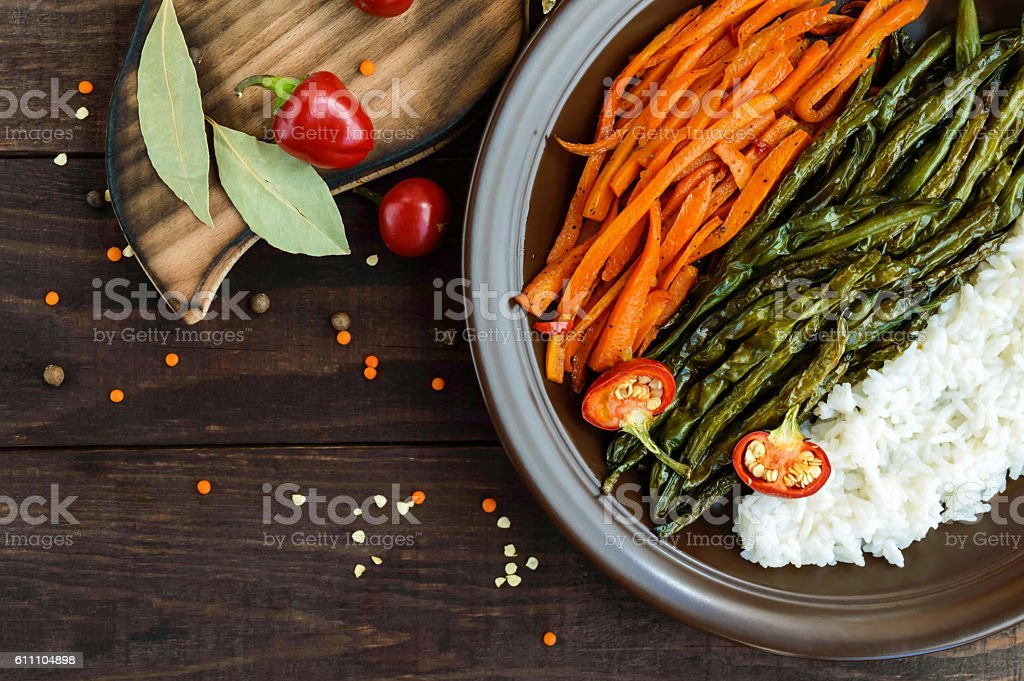 Baked vegetables (asparagus beans and carrot), boiled rice stock photo