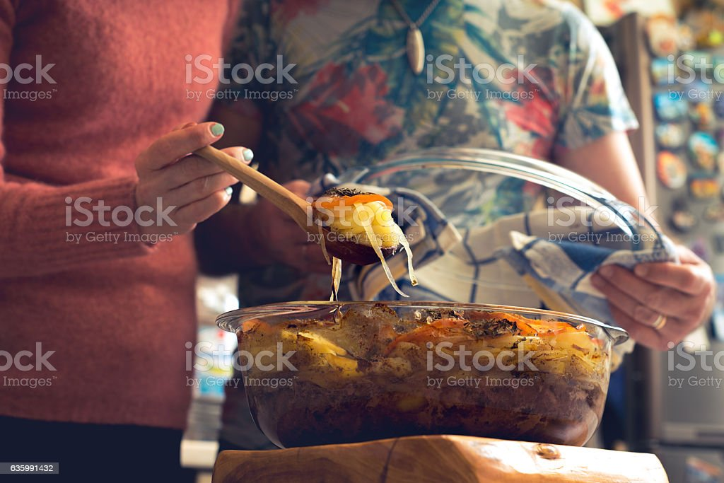 Baked vegetables on spoon and glass bowl with meal horizontal Lizenzfreies stock-foto